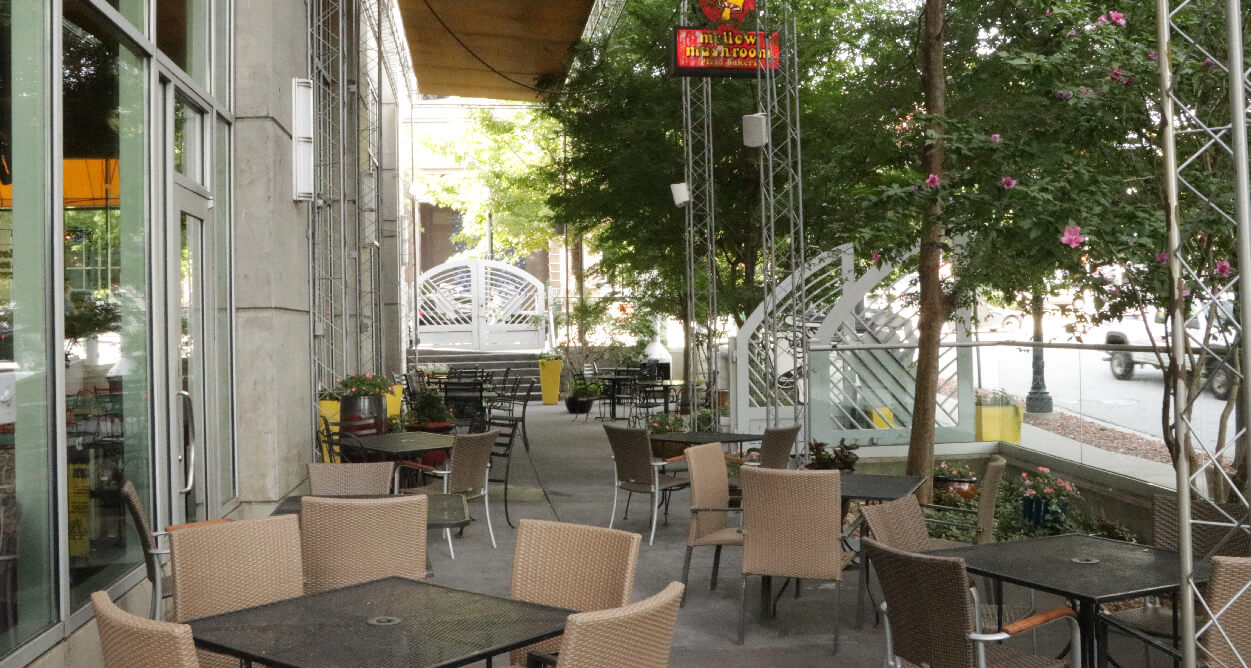 Mellow Mushroom Downtown Atlanta - outdoor patio in front of store with fire place and mellow mushroom gates