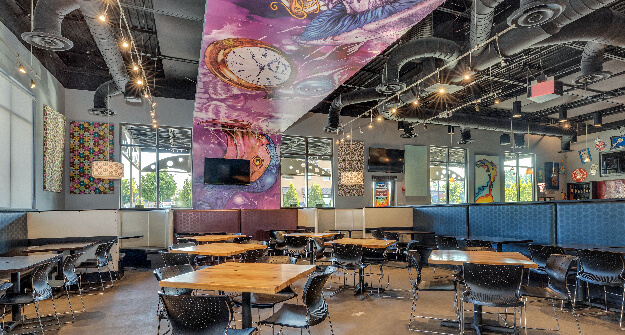 Mellow Mushroom Hamilton Place- Chattanooga main dining tables and booths overhead mural