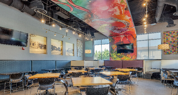 Mellow Mushroom Hamilton Place- Chattanooga main dining tables and overhead mural