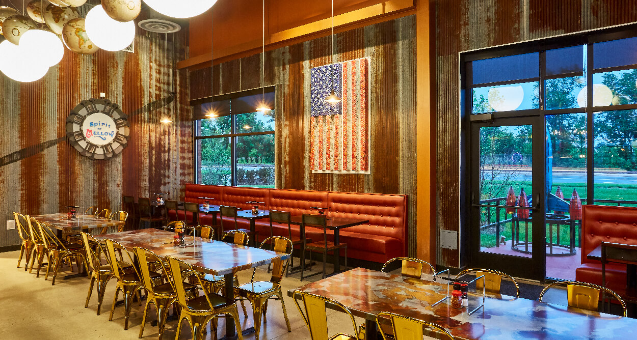 Mellow Mushroom Chantilly - metal sheet walls feature tables metal chairs American flag red booths