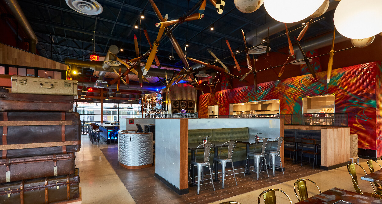 Mellow Mushroom Chantilly - restaurant interior metal backed booths tall stack of suitcases aviation theme propellers hanging from ceiling host stand