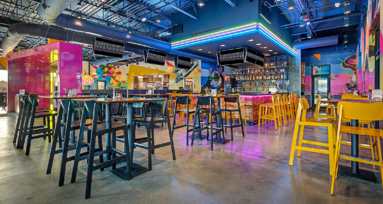 Mellow Mushroom Cottleville - yellow and black tall chairs high top tables concrete floors exposed industrial